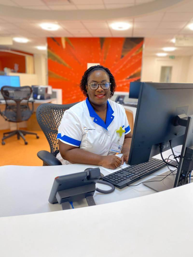 Employee of Curaçao Medical Center sitting in front of a computer, ready to help patients & visitors.
