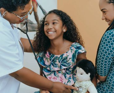 Doctor at the Curaçao Medical Center providing care to a young patient while serving with love.