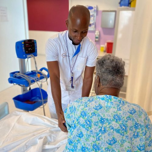 Male doctor at the Curaçao Medical Center providing care to an elderly patient while serving with love.